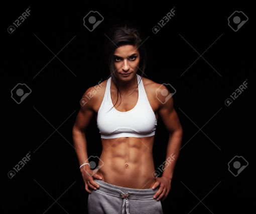 43375562-Shot-of-a-strong-woman-with-muscular-abdomen-in-sportswear-Fitness-female-model-posing-on-black-back-Stock-Photo