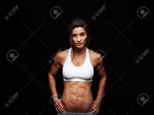 43474271-Studio-portrait-of-a-sporty-young-woman-isolated-on-black-background-Confident-fitness-model-with-pe-Stock-Photo