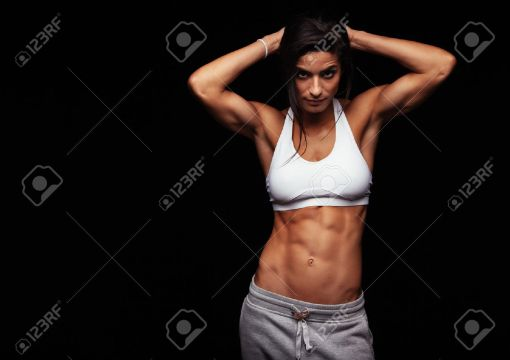43852658-Muscular-woman-wearing-fitness-clothing-posing-against-black-background-Caucasian-female-model-with--Stock-Photo